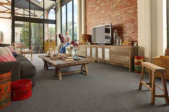 Vintage pieces of different ages can work alongside newer finds for an eclectic look. A foundation of charcoal carpet with a subtle texture of a heathered yarn brings the look together.  Credits - Carpet: Godfrey Hirst Carpets; Large coffee cans, centre cushion, larger bottles and wooden crates: Izzi & Popo; Arm chair: Reissued; Other cushions: Linen House; Smaller bottles: Amalfi Homewares.