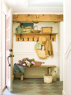 Charming cottage style entryway with hooks for hanging, a shelf for displaying, and a painted wooden bench for sitting or quick drop offs.