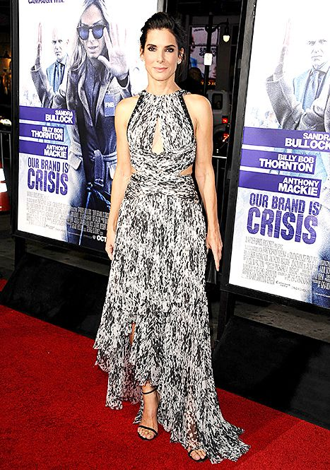 Sandra Bullock attends the premiere of Our Brand of Crisis -  in a black and white, silk chiffon J. Mendel dress, complete with grommet accents, cutouts on the side, top, and back, cutouts at the bodice and her back, and a draped skirt. She added Jack Vartanian ear climbers, a box clutch, and minimalist ankle-strap sandals by Stuart Weitzman.