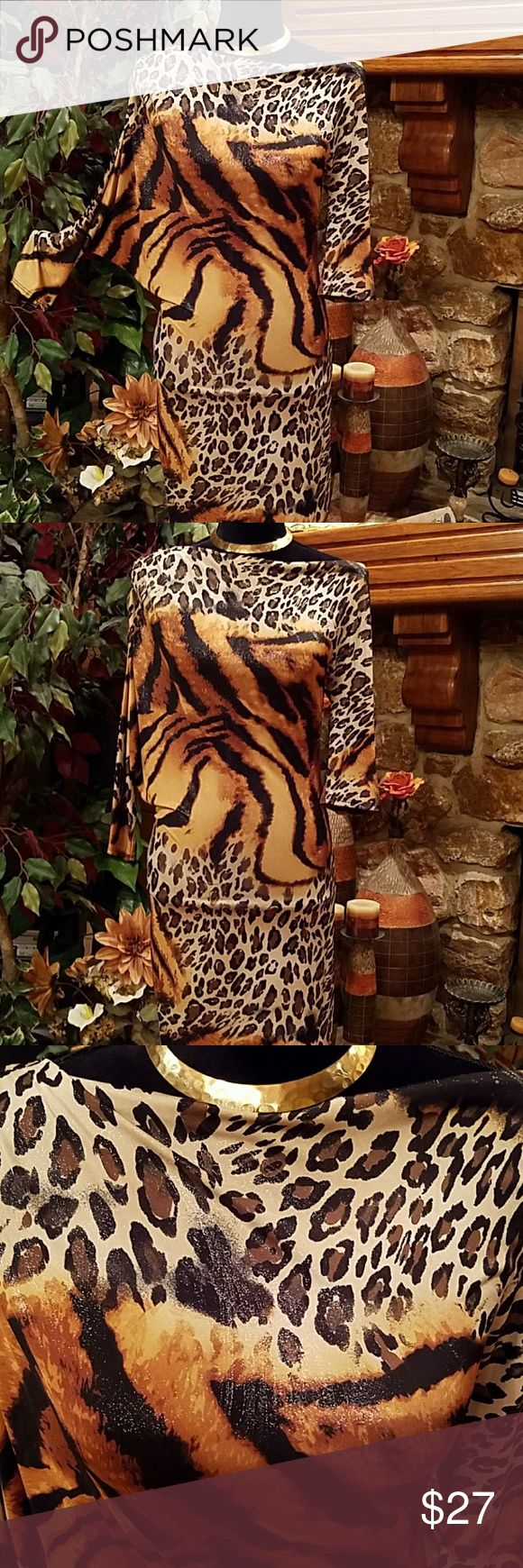 """Metallic Animal Print Dress NWOT/This dress has  an asymmetrical neckline and sleeves. It can be worn both on or off the shoulder. The right sleeve is 19"""" and has a bat wing design. The left sleeve is 15"""". Lying flat, the length is 33"""", the natural waist is 14"""". The bust line is quite roomy due to the unique design, 15"""" plus. Fabric content: 92% nylon, 8% spandex. Hand washable. Accessories not included. Offers welcomed. TRUE LIGHT Dresses Asymmetrical"""