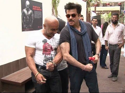 CHECKOUT Anil Kapoor showing his bisceps at the opening of THE RED GYM.