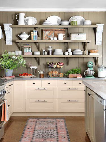 Amazing Kitchen Makeovers~ The cabinets and surfaces were swapped in favor of Ikea units painted Barely Beige by Benjamin Moore and topped with zinc. Above, open shelving displays collectibles alongside everyday dishware. The ceiling is painted Creamy White by Benjamin Moore.