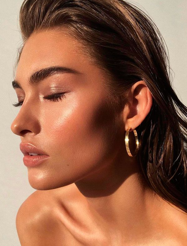 Uma dica para ter a pele bronzeada o ano todo é  a escolha dos iluminadores dourados. Além de iluminar a pele, eles ajudam no bronze poderoso. Os líquidos e cremosos funcionam melhor porque dão o efeito glossy e funcionam super bem com o bronzer.