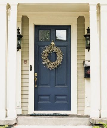 Navy blue front door on a tan house with white trim. Pretty!