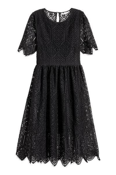 Kanten jurk: Een knielange kanten jurk met korte mouwen, een nauwsluitend lijfje en een heel wijde rok. De jurk heeft een splitje met een knoop in de nek, een naad in de taille en een blinde ritssluiting opzij. Gevoerd met een licht transparante kwaliteit.