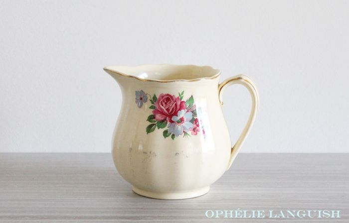 Lovely cottage chic cream/pale yellow pitcher featuring a pink rose and blue floral motif. Gold trim. Ribbed body and scalloped edges.