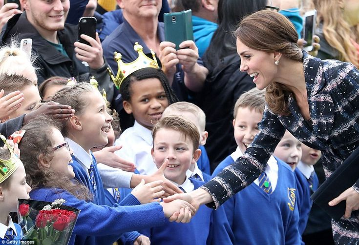 Kate receives a handshake from a young pupil from St Philips School in Salford, who looked...