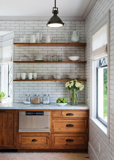 Floating chestnut wood shelves, everyday dishes, antique bronze hardware and white subway tile with gray grout.