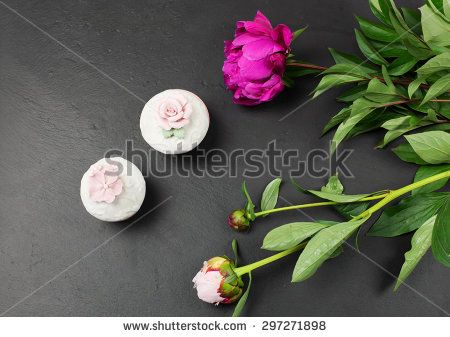 peomies and little perfumery boxes over slate background