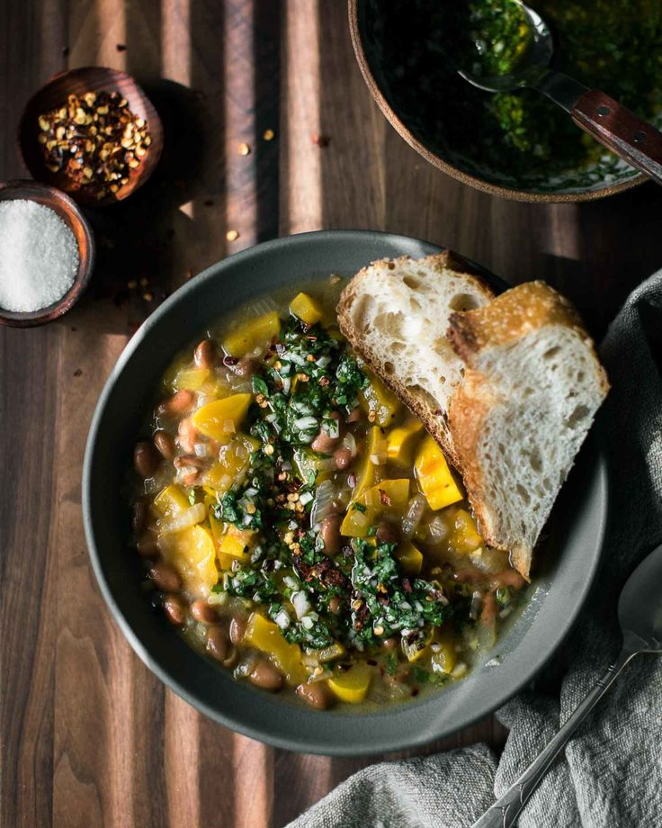 An easy, vegan squash stew that features pinto beans cooked with delicata squash and topped with homemade chimichurri sauce.