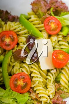 fresh healthy homemade italian fusilli pasta salad with parmesan cheese,pachino cherry tomatoes, black olives and mix vegetables ,dressed with extra-virgin olive oil and pesto sauce