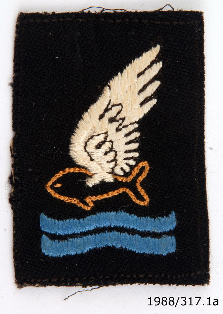 Cloth badge for the Goldfish Club - a worldwide association for those who have escaped an aircraft by parachuting into water. From the collection of the Air Force Museum of New Zealand.