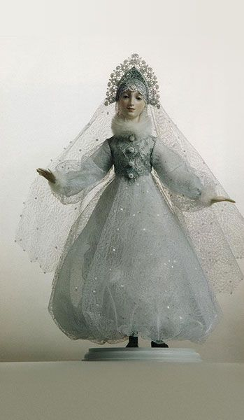 "Snow Maiden doll by Alexandra Koukinova  Biscuit porcelain.The three-layer gas skirt is covered with a lacy hand painted grid and is trimmed with a velvet string. The bodice is executed of silver or gold laces – ""Chantilly"". The ""kokoshnik"" is made of gold and silver laces. Furnish is executed by beads and strasses.Hair – natural mohair.   Hand painting of a face."