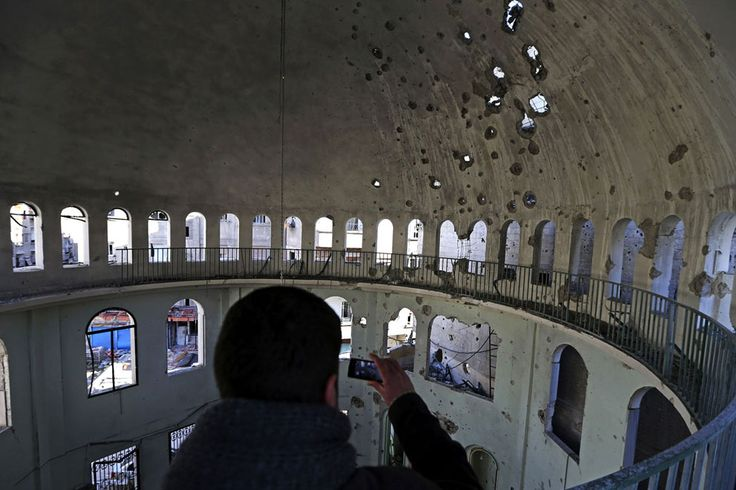 A Free Syrian Army fighter photographs inside a mosque damaged by shells fired by Syrian Army in the Haresta neighborhood of Damascus, on January 29, 2013. (Reuters/Goran Tomasevic)