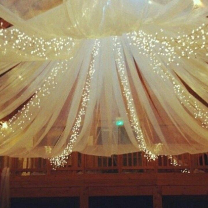 #Wedding #Decorations #DIY - This looks like it might be simple to mimic; sheer sheet or curtain and several strings of light gathered at a point and flared outwards at the bottom. Could be an outdoor decor idea :)
