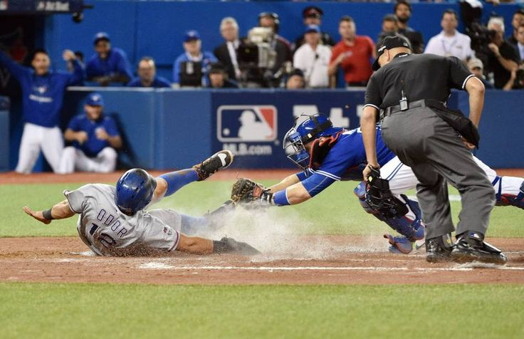 Oct 9, 2015; Toronto, Ontario, CAN; Texas Rangers second baseman Rougned Odor (left) scores a run past the tag of Toronto Blue Jays catcher Russell Martin in the second inning in game two of the ALDS at Rogers Centre. Mandatory Credit: Nick Turchiaro-USA TODAY Sports