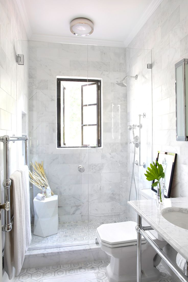 All-white marble bathroom with glass shower