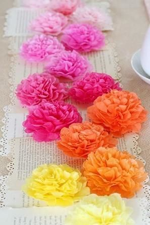 DIY paper flower table runner using pink, orange and yellow floral decorations on book pages.