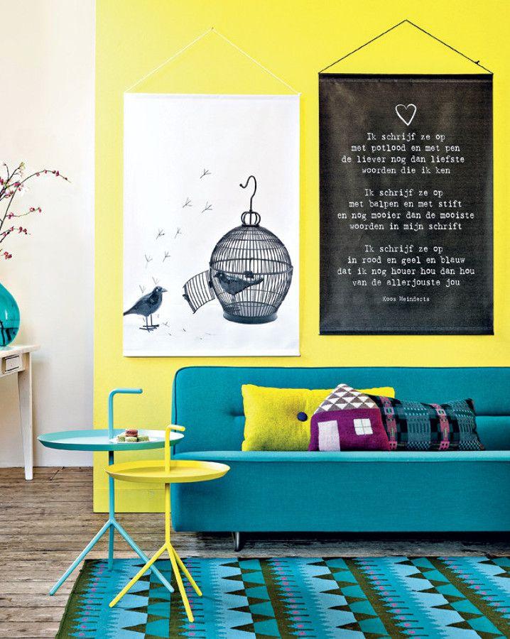 Comedor con pared amarilla y sofá y alfombra en tonos turquesa