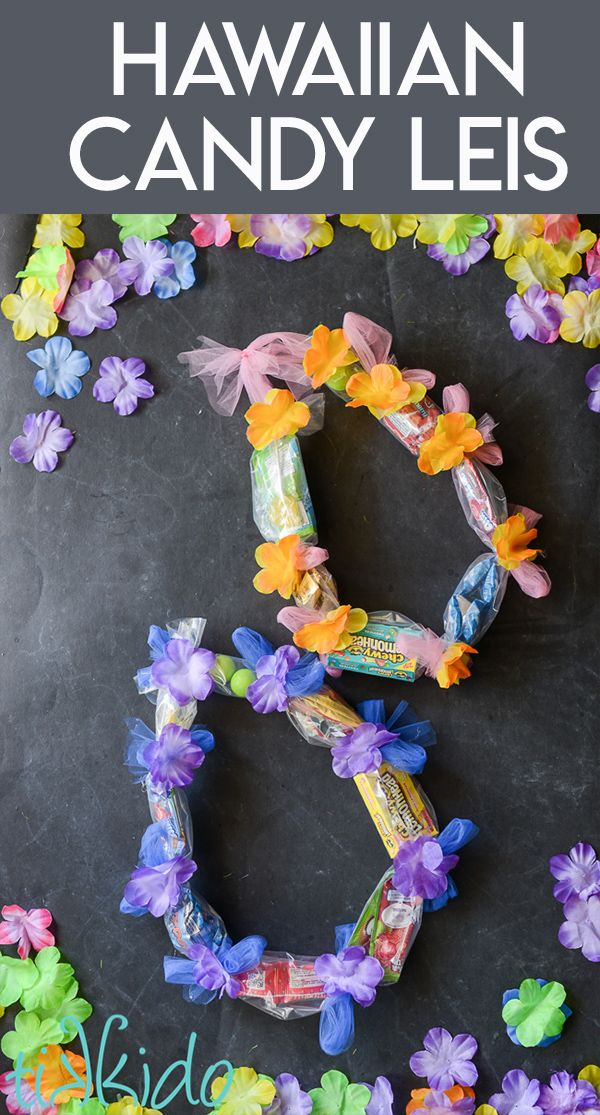 Two candy leis on a black chalkboard background su…