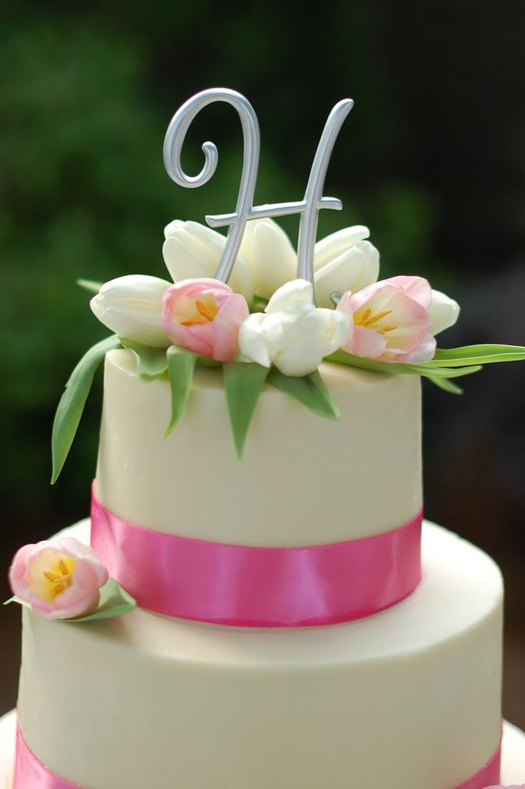 I said tulips wouldn't look nice on a cake, but this is really sweet and cute. Tulip cake. Tulips placed around the cake topper with ribbon band.
