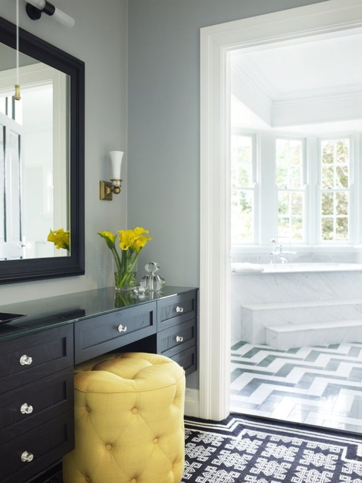 Black & white chevron tiled bathroom with dressing table & yellow upholstered stool seat