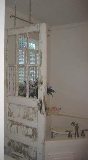 Oude gepimpte deur met glas = douch of bad afscheiding.