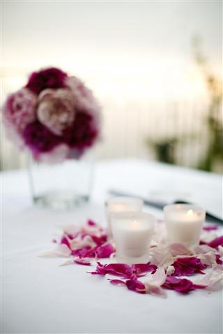create table centrepieces with candles and petal confetti to match your flowers