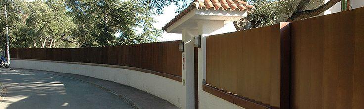 Construcción de valla de acero corten sobre muro de obra compuesta por lamas verticales en U y cubre muro. La puerta peatonal es igual a la valla, la puerta del parking es corredera y queda disimul…