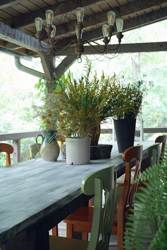 A rustic Fall log cabin porch with gathered grasses in antique crocks