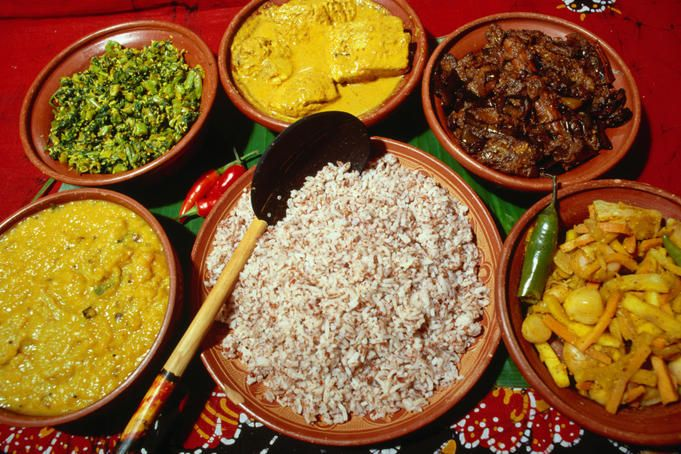 A typical Sri Lankan meal. Clockwise from left; a dhal curry, green leafy vegetable, a chicken curry, fried eggplant, pickled vegetables and red rice in the centre.