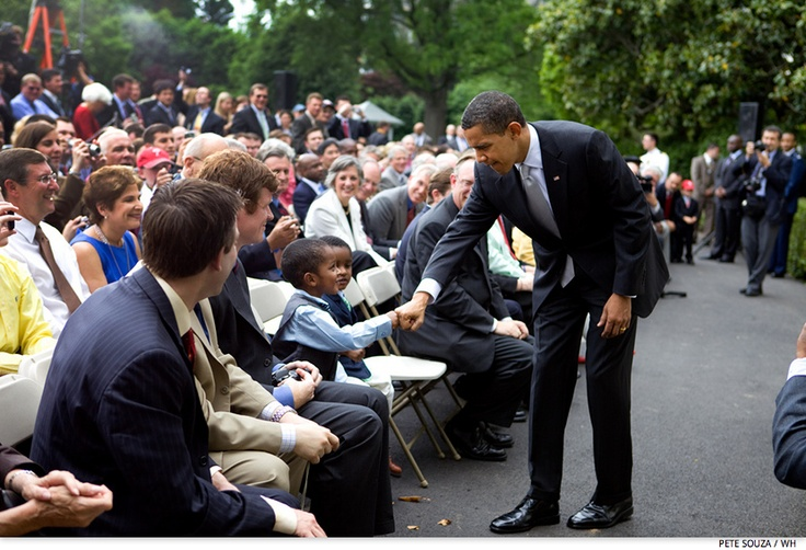 Obama bumps fists with a child in the crowd following the ceremony honoring the 2008 World Series Champion Philadelphia Phillies on the South Portico of the White House, May 15, 2009.