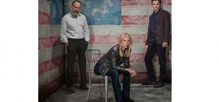 Claire Danes als Carrie Mathison in der Serie Homeland mit ihren Kollegen vor einer US-Flagge.