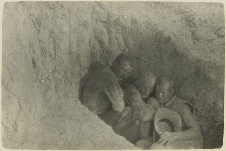 Sheltering from bursting shells, [showing three Anzac soldiers huddled together sheltering in a shallow trench, June? 1915] J.P. Campbell | Flickr - Photo Sharing!