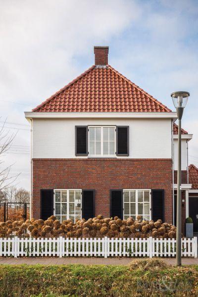 Rode pannen, rode bakstenen,  een wit element op de voorgevel en witte hekjes bij de voortuin. Klassieke woning, jaren-dertig woning.