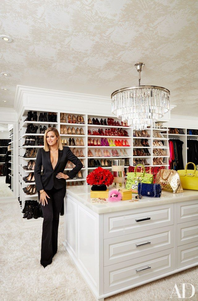 Khloé Kardashian in her vast master closet; the chandelier is by RH, and the ceiling is lined in a Schumacher wallpaper   archdigest.com