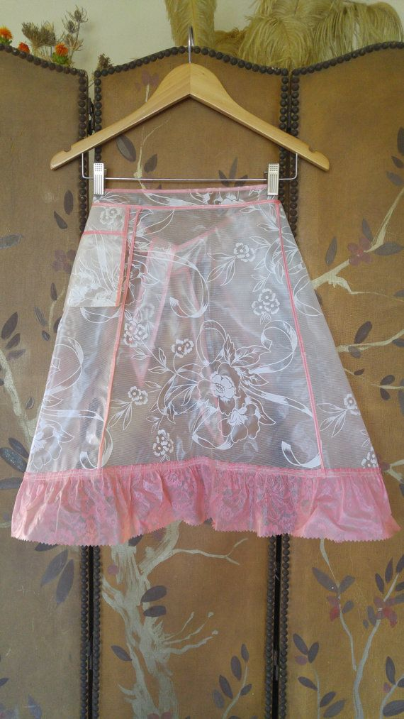 One of a kind 50s vinyl / plastic apron. Kitsch apron with pink lace print hem and pink trim. Pocket on front. Clear front with white flowers and ribbon print. Ties at sides. Perfect for bathing a baby!! waist band 21, ties 16 long each. apron length 21 1/2