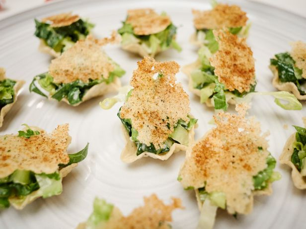 Caesar Salad Taco Bites : No longer is Caesar salad a knife-and-fork-needed dish; Giada uses tortilla chip scoops to hold her classically dressed salad, which she finishes with savory Parmesan crisps.
