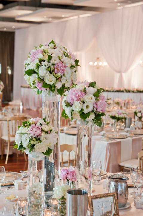 Tall floral centrepieces in clear vases.