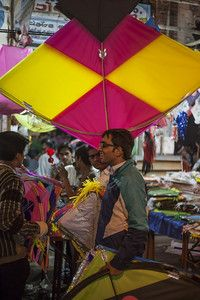 Boy carries his set of kites and big kites for the festival of Makar Sankranti or Uttarayan in the old area Khadia of Ahmedabad in Gujarat, India