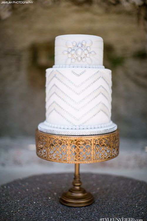 Great Gatsby inspired wedding cake. White wedding cake with silver sparkle on a vintage gold cake stand.