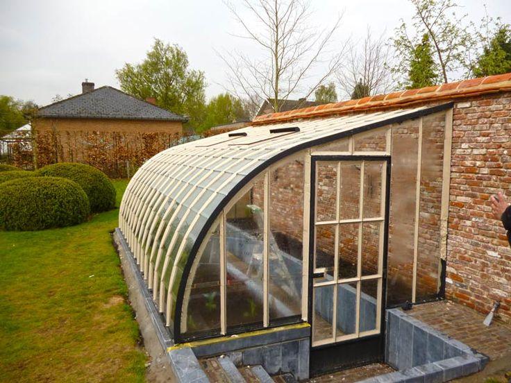 Serre adossée verre et fer forgé: une serre adossée peut être construite par DBG Classicsdeplusieurs façons.    Cette serre de jardin est un modèle sur mesure en fer forgé, encastrée dans le sol et construite contre le mur de jardin du client.    À droite et à gauche du long passage intérieur, il y a une petite serre pour