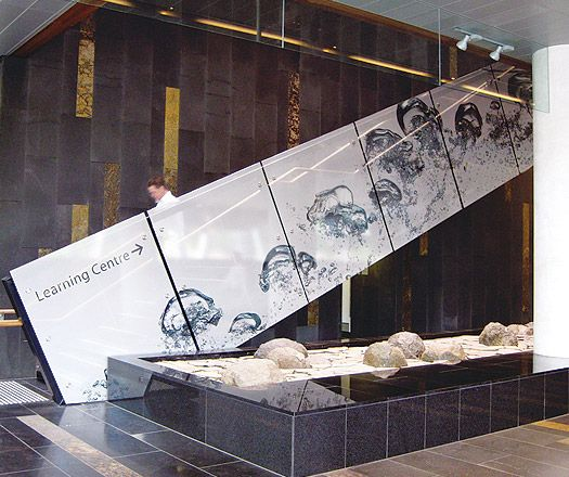 large scale graphics applied to glass. Here, a the glass stair railing is an opportunity to direct and inform.