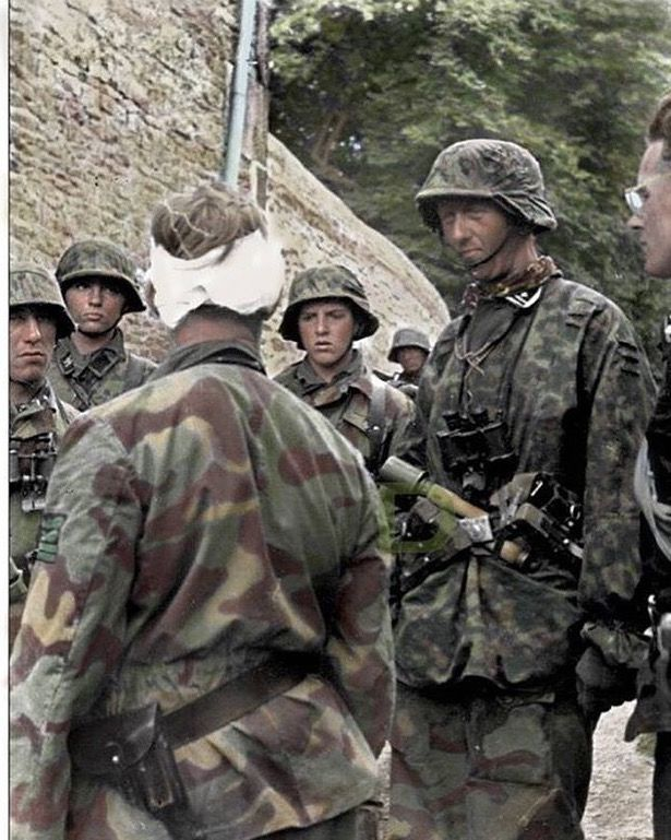 SS-Obersturmbannführer Max Wünsche (with the bandaged head), Rgt. Komm. of SS-PzRgt 12 visiting survivors of III.ZUG 15./25 SS PzG. Rgt. at Rots, Normandy on June 9, 1944.  Partly seen on the right side of the image is SS-Hauptsturmführer Rudolf von Ribbentrop, 3. Kompanie, I./SS-PzRgt 12, son of German foreign minister von Ribbentrop