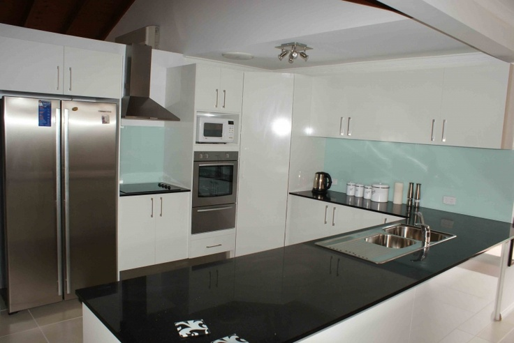 black benchtop with white cabinets