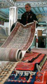 Dans le souk de Kairouan, un marchand déroule un tapis