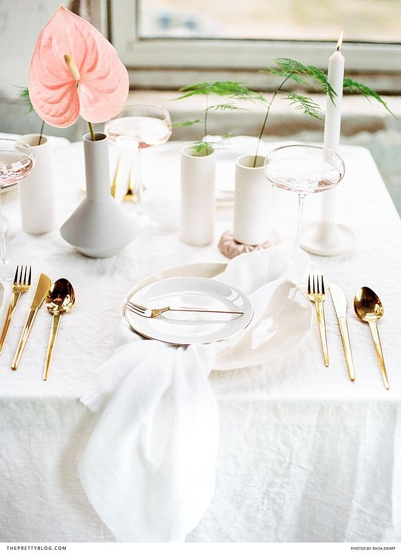 Minimalistic table setting with white linen, crockery and gold cutlery. Hints of pink and green