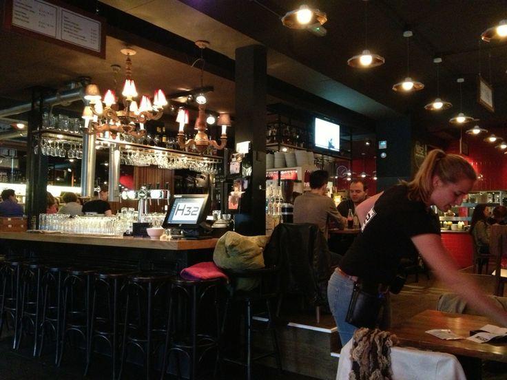 """Een eigentijds café met keuken, waar beleving, gastheerschap en kwaliteit een rode draad vormen.   Geniet van onze open keuken… Een bar waar je niet omheen kunt… Een heerlijk verwarmd terras… Openingstijden waarin ALLE eet- en drinkmomenten mogelijk zijn… En…een superuitzicht op het Osse centrum """"de Heuvel""""  Al onze gerechten worden op authentieke wijze """"live"""" bereid in onze steenoven.  smaaksensatie"""