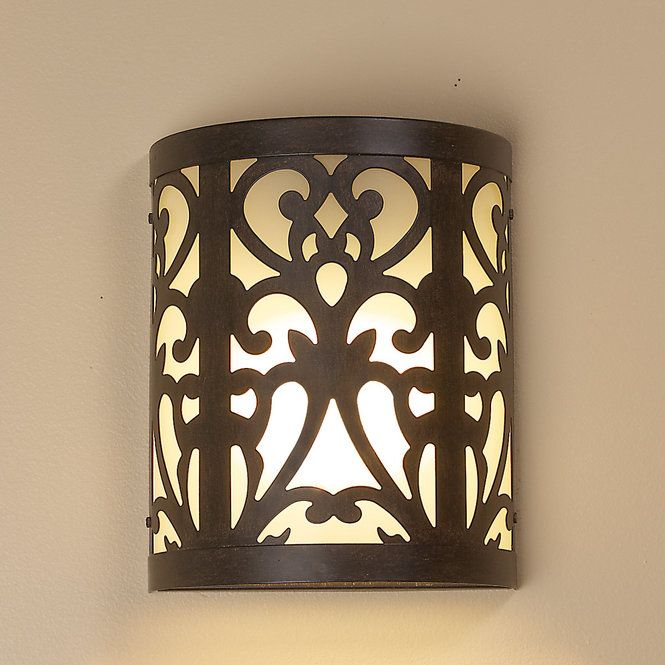 "A diffused glow radiates through thick curved frosted buttercream glass and bronze metal scrollwork for a unique look in rustic or modern homes! 13 watt GU24 compact fluorescent bulb included. (10""Hx8""Wx4""D)"