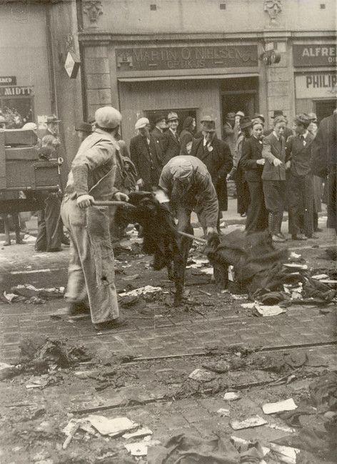 Utenfor NS-huset, i Christian Michelsensgate 4, etter at inventar og utstyr fra kontorene var kastet ut,  og satt fyr på, 8. eller 9. mai 1945. Opprydning. Samme sted i dag.  Fotograf ukjent.  Fra samlingen etter Waldemar L. Hansen